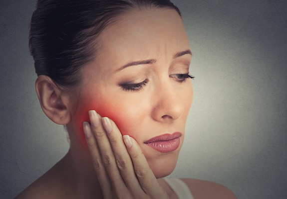 Distressed woman holding her jaw in pain