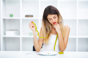 Woman with single pea on her plate