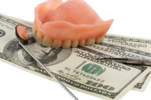 $100 bills under denture and dental tools