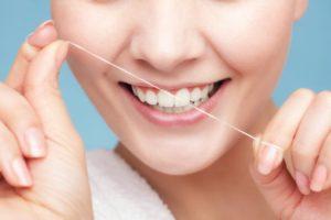 happy woman flossing her teeth