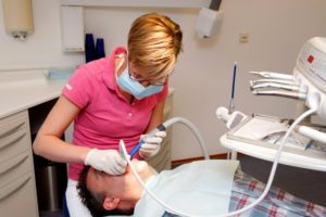 dental hygienist pink shirt cleaning teeth
