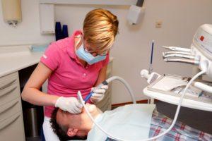 dental hygienist pink shirt cleaning teeth