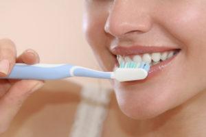 woman smiling while brushing teeth