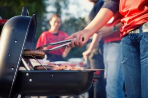 woman grilling burgers red shirt
