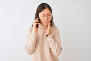 person with a toothache on the phone
