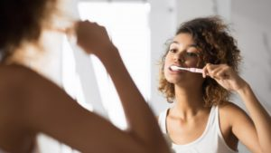 person brushing their teeth and taking care of their dental crowns