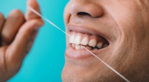 closeup of a person flossing their teeth