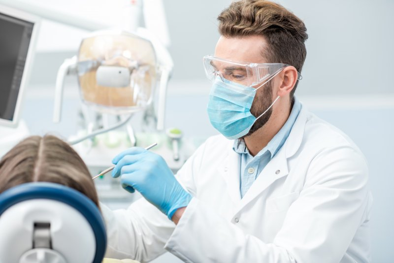 A dentist wearing a face mask, gloves, and protective eyewear while caring for a patient