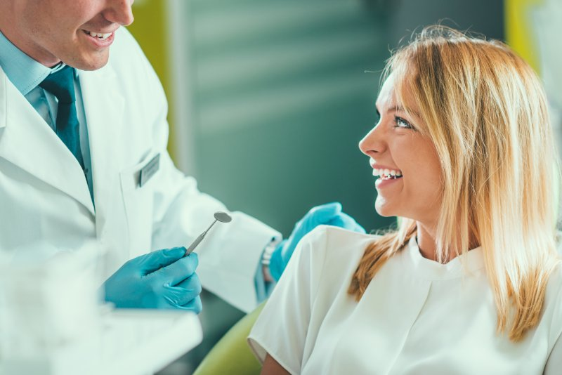 a female patient looking at her cosmetic dentist as he explains which treatments will be best for her smile